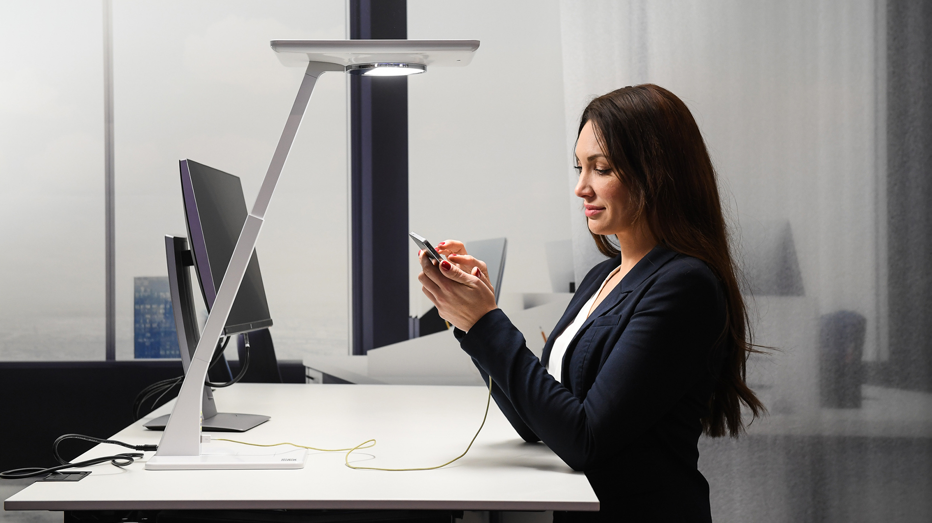 A woman is standing at a desk lamp